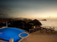 View from St Lucia's Best Holiday Villa Rental Entertainment level over the pool at Sunset towards Pigeon Island